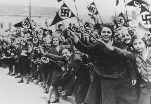 Members of the League of German Girls wave Nazi flags in support of the German annexation of Austria. Vienna, Austria, March 1938 (via United States Memorial Holocaust Museum)